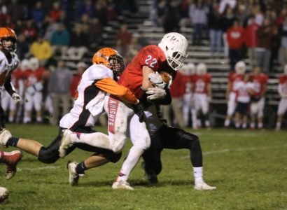 Hamilton's Andy Hernanadez hangs on to Wall Twp Running Back.  Photo by Donna Brihnn
